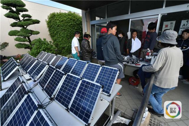《日本震区灾民用太阳能板充电手机》